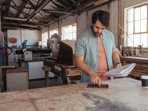 builder with tablet in workshop